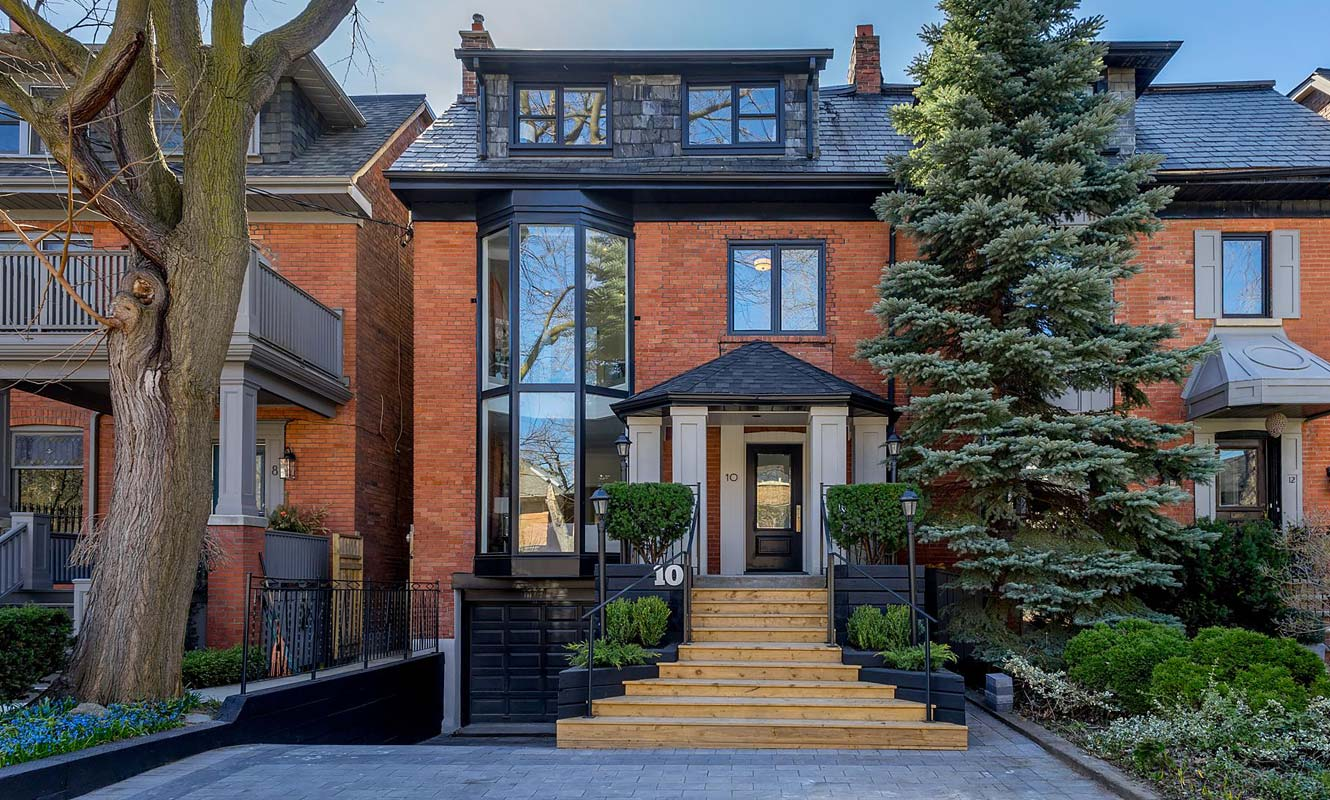 The exterior of a semi-detached home in Central Toronto, with two large trees in the front. Listing by realtor Boris Kholodov.