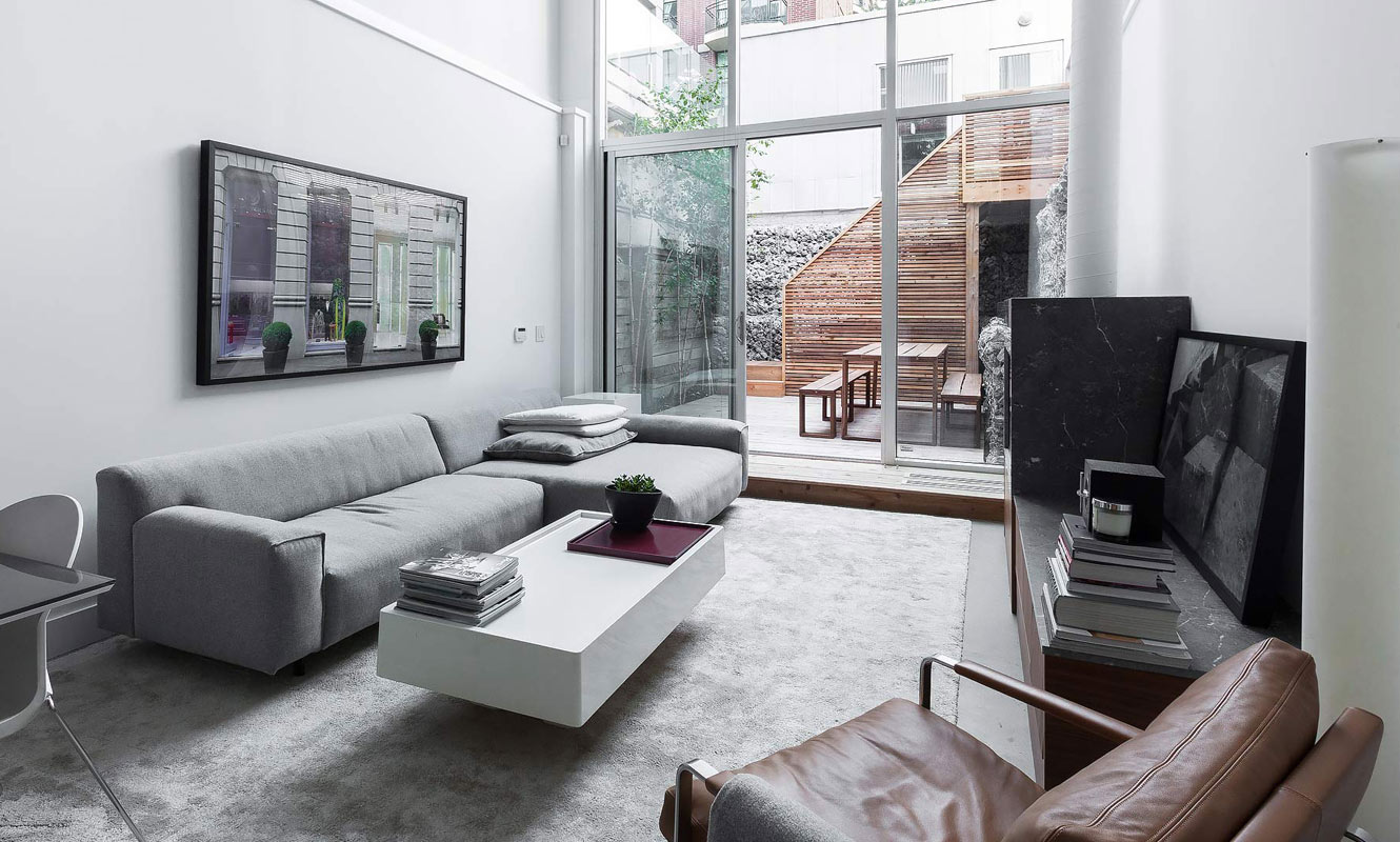 A minimalistic modern interior of a luxury home in downtown Toronto with floor-to-cieling windows that span two levels.